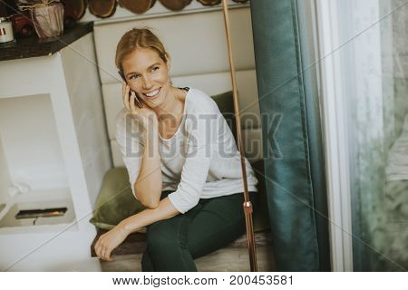 Young Woman Sitting In Cafe And Using A Cell Phone With A Smile On His Face