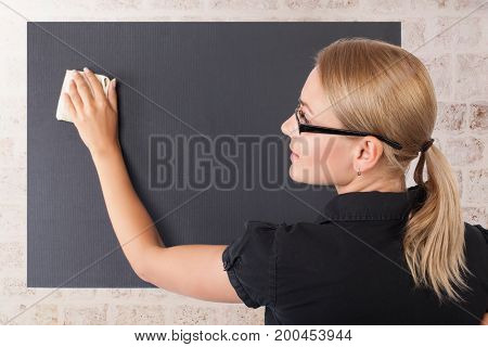 Student girl cleaning blackboard in the classroom, text space on the chalkboard, education in the university, getting knowledge in the high school