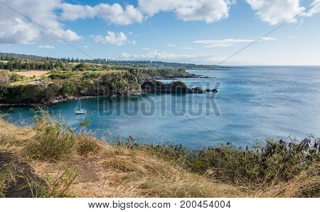 A yacht is anchored in a cove on the Northwest Maui shoreline.