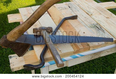 building tools hammer, axe, hacksaw frame, lie on the light boards in the garden.
