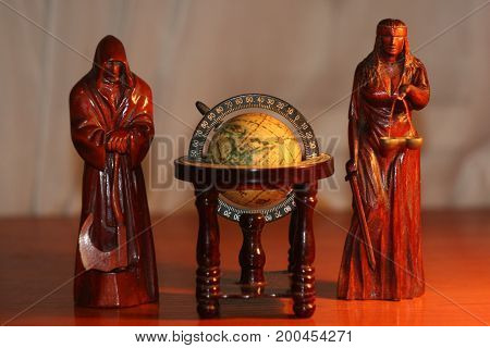 A composition of wooden statuettes characterizing the judge and flogging the world.