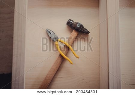 Vintage Hammer, Pliers On A Wooden Background Close-up