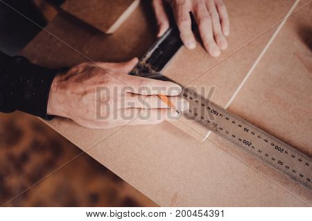 A Carpenter Uses A Square For Marking A Hole In A Furniture Part