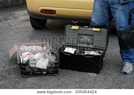 Service man legs wearing protective wear and open tool boxes outdoor cropped photo