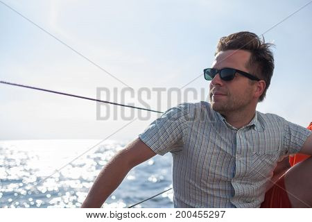 Young caucasian sailor relaxing happily on sailboat yacht. He loooks aside and dream. Active summer vacation.