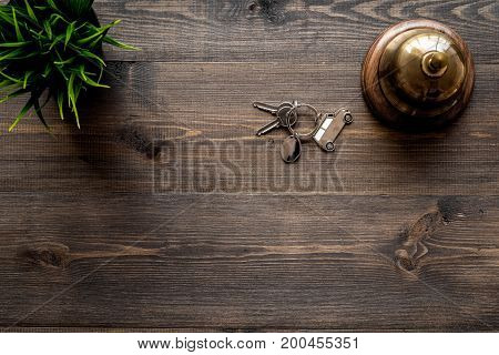 Hotel service bell on dark wooden table top view.