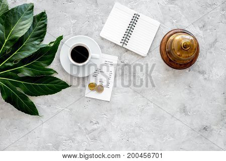 Ask for the bill at cafe. Service bell near coffee, check and coins on grey stone table top view.