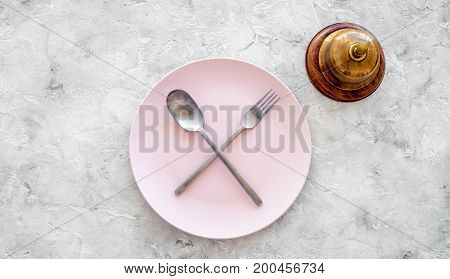Meal is over. Ask for the bill. Plate with crossed spoon and fork on grey stone table top view copyspace.