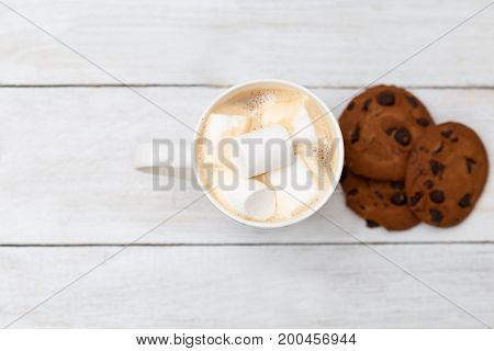 Latte with marshmallow and chocolate cookies on a white wooden background