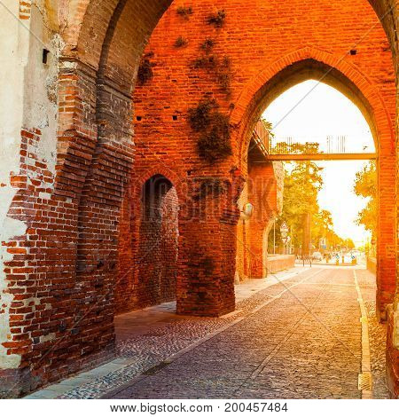 Defensive wall surrounding the small old town of Cittadella in Italy at sunrise. Entrance gate in the wall of red brick illuminated by sun.