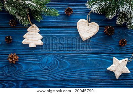 New year's background. Christmas toys, spruce branches, pine cone on blue wooden background top view.