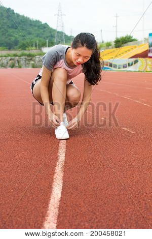 Girl Tightening Shoelaces On A Jogging Track