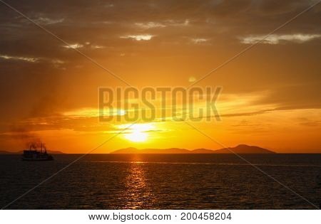 Beautiful sunset above the sea/Dramatic orange sunset with clouds. Horizontal seascape with boats