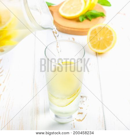 In A Glass Beaker, A Cold Lemonade Is Poured From A Jug On A White Wooden Background Surrounded By L