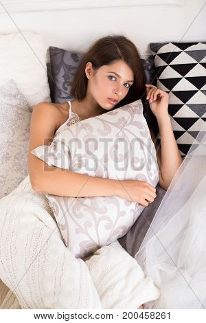 Peaceful Sleep. Top View Of Attractive Young Woman Covered Pillow And Smiling While Lying On The Bed