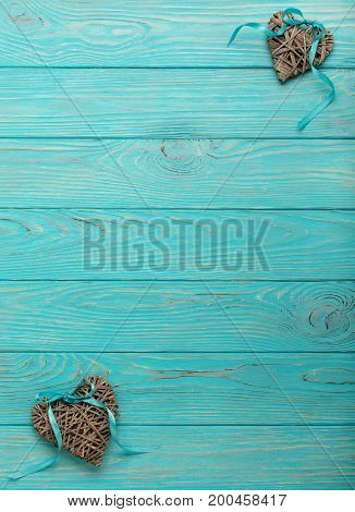 Decorative wicker hearts of gray color with a blue ribbon on a wooden background. Top view.