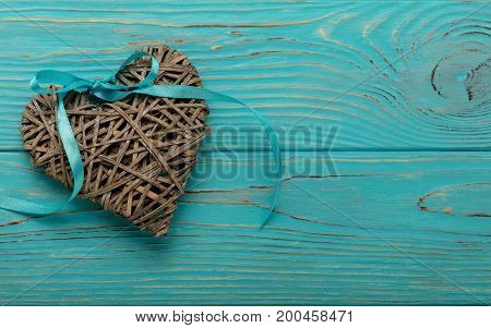 Decorative wicker heart of gray color with a blue ribbon on a wooden background. Top view.