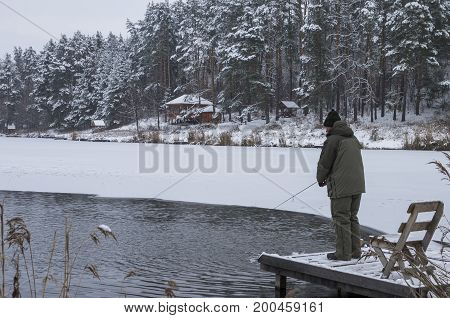 Winter Fishing. Fisherman In Action. Lake In Forest