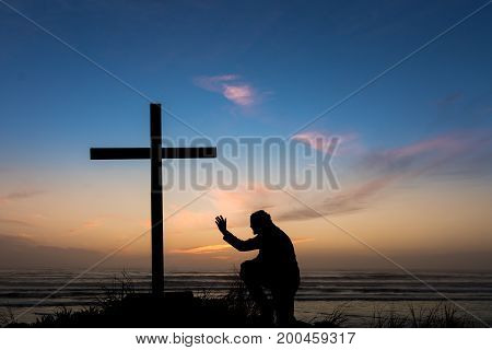 Man praying with his hand up by a black cross on a beach with a dusk sky sunset behind it.