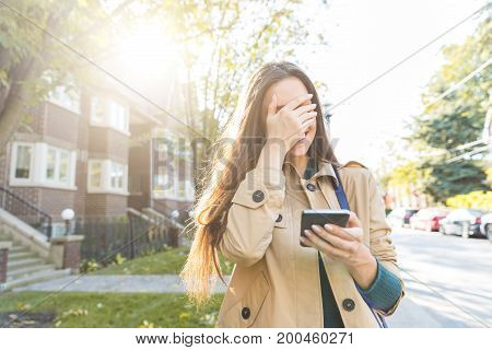 Woman With Smartphone Laughing And Covering Face With Hand