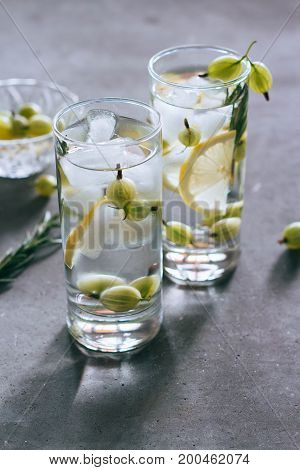 Lemonade with ice in a glass cup opposite light from lemon gooseberry rosemary on a concrete background