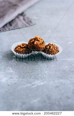 Natural useful raw candies from prunes with pecans in cocoa powder