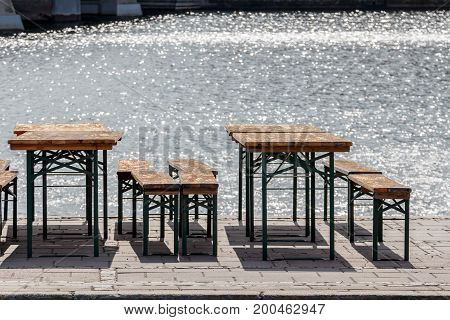Public Beer Garden Old Vintage Chairs And Seat Benches, Tables At Sunny Day Near Water