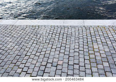 Monotone Gray Brick Stone pavement pier beside blue sea