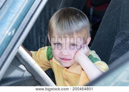 Little boy sitting in the car driving. One hand props her cheek. The other hand held behind the wheel and looking at us. He's thoughtful and smart look. He dreams about something.