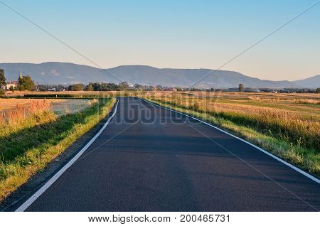Summer rural landscape. Asphalt road with mountains and village in the background.