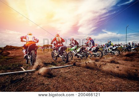 Racer on a motorcycle participates in motocross prepare for start against a team of rivals motocross. Concept active extreme rest. ray of light sunset.