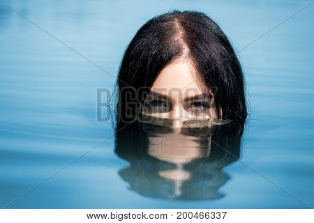 A Sexy Woman Or Girl, Floating In The Water, Only The Eyes Are Visible From The Water. Concept Of Le