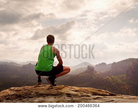 Tourist in green singlet and black shorts in squatting position on a rock enjoy scenery. Long valley full of creamy fog after rainy night