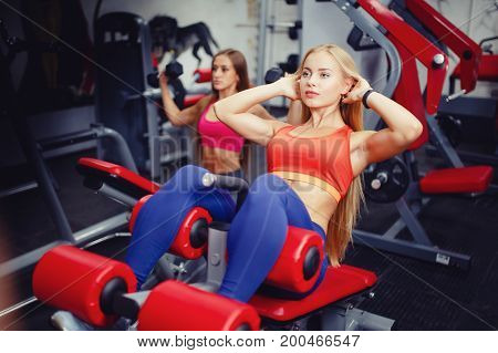Close-up of a young girl in a sports hall shakes a press sit-ups on a sports simulator, in the background a girl is doing exercises. Concept of weight loss.