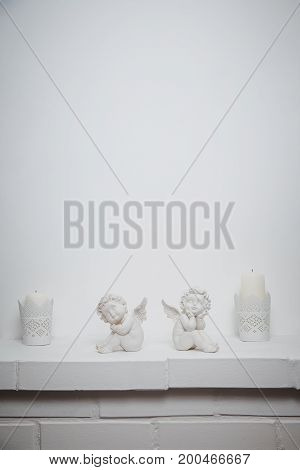 White abstract plaster background with angels and candles, brick underneath. copy space