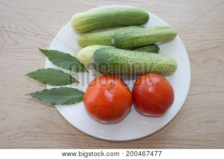Fresh organic vegetables on table. Include fresh organic vegetables and Cucumber on wooden floor. Green Cucumber. Summer frame with fresh organic vegetables on wooden background