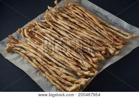 Traditional Italian Snack, Bread - Grissini. On A Dark Stone Table.