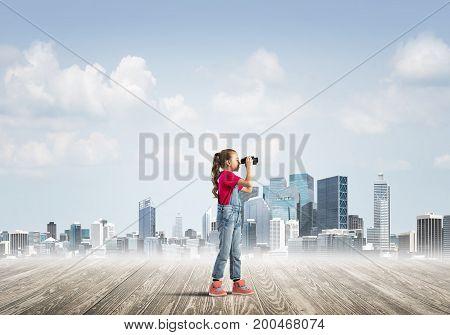 Cute kid girl standing on wooden floor and looking in binoculars