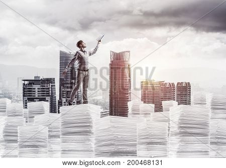 Side view of man in casual wear keeping hand with book up while standing on pile of documents with cityscape and sunlight on background. Mixed media.