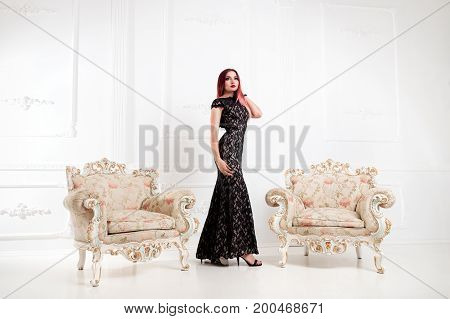 Elegant Woman Or Girl In Evening Black Dress Is Standing In An Aristocratic Vintage White Hall With