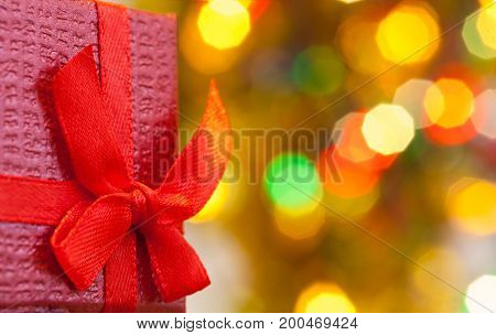 Box with christmas gift with red bow and christmas bokeh light abstract holiday background