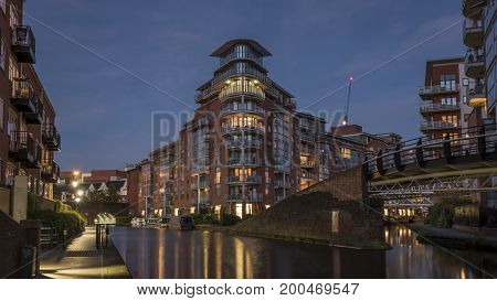 Modern apartment buildings, lit up at dusk, overlooking an urban waterway, canal, in Birmingham, England, UK