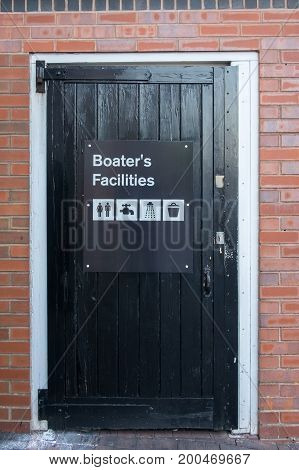 A black, wooden door, with a sign saying 'Boaters Facilities', and four icons showing the facilities on offer