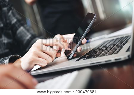 Close Up View Of Businesswoman Working On Modern Smartphone And Laptop. Closeup View Of Female Hands