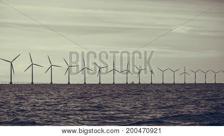 Wind turbines generator farm for renewable sustainable and alternative energy production along coast baltic sea near Denmark. Eco power ecology.