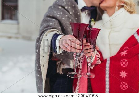 bride and groom in a winter holding glasses with red mulled wine