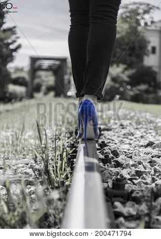 A girl with high heels walking through the rail
