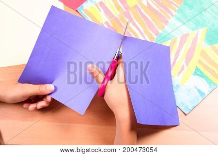 Kid's hands cutting colored paper with scissors