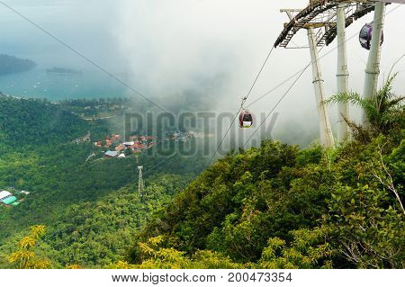 Cable car tower fixed atop a hill with the cable and cablecars going down. The sea is visible in the distance with cloudy skies and fog