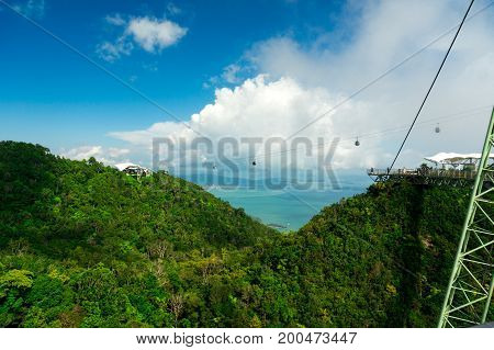 Cable car cables and supporting tower placed on a high tree covered mountain. The blue sea is visible in the distance. Fog and cloudy skies add atmosphere to this shot of Langkawi, Malaysia